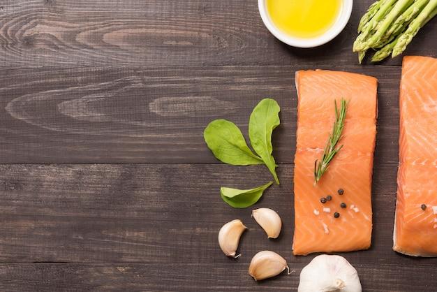 Свежее филе лосося со специями на деревянном фоне