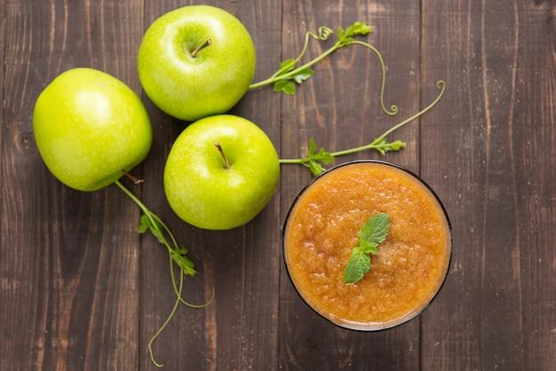 木製のテーブルの上から見る緑のリンゴのスムージー
