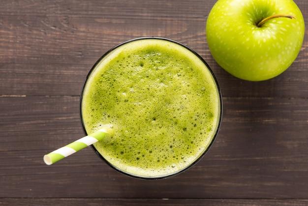 素朴な木製の背景にアップルと健康的な緑のスムージー