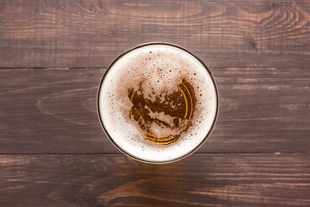 木製の背景にビールのグラス。上面図