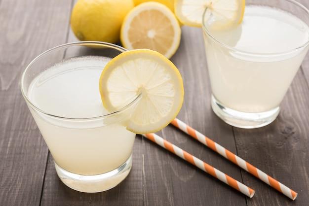 Лимонад со свежим ломтиком лимона на деревянном столе