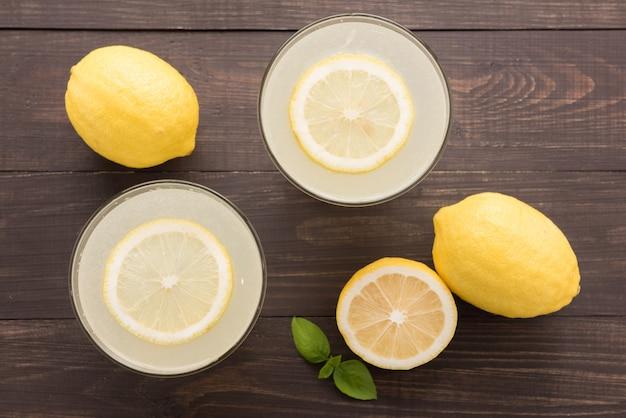 Лимонад со свежим ломтиком лимона на деревянном фоне
