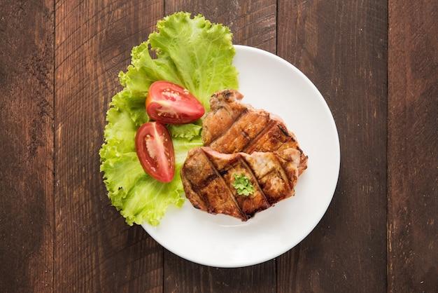 皿に野菜とステーキのグリル。