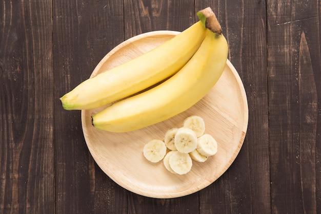 木製の背景に新鮮なバナナ