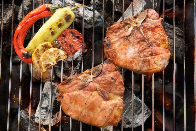 燃えるようなバーベキューグリルでポークチョップステーキと野菜