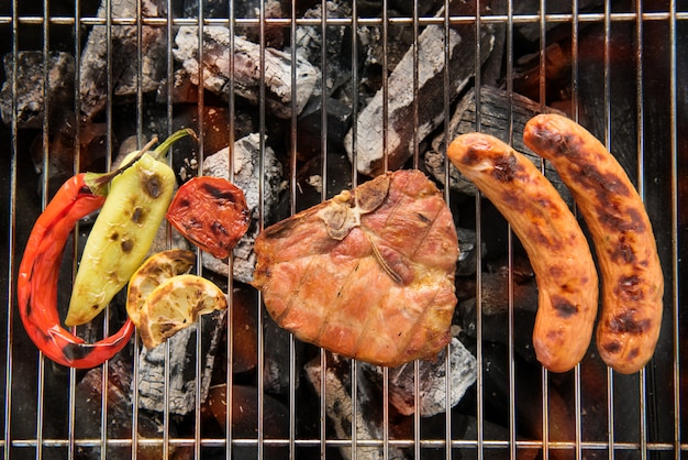 ポークチョップステーキと野菜の燃えるようなバーベキューグリルでのソーセージ添え。