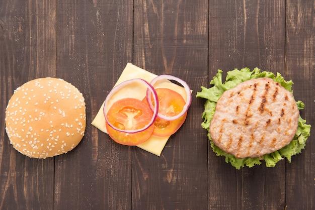 木製テーブルの上に水平トップビューバーベキューハンバーガーパーツ。