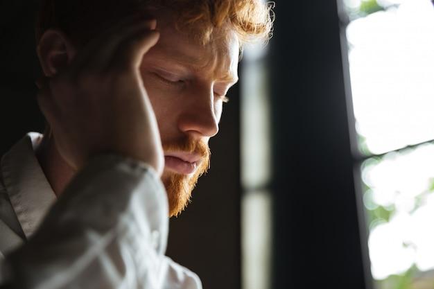 彼の頭に触れる、頭痛を持つ若い赤毛の男のクローズアップの肖像画