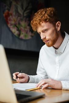 Портрет мышления молодой рыжий мужчина, глядя на ноутбук на рабочем месте