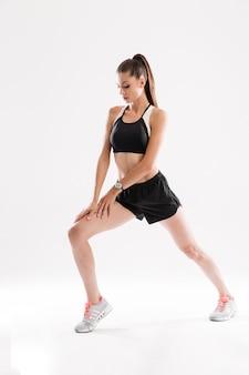 ストレッチ体操を行うフィットネス女性の完全な長さの肖像画