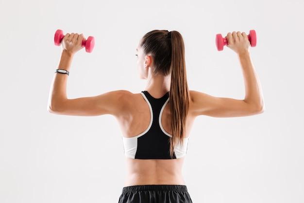 ダンベルを保持している健康的なスリムなスポーツウーマンの背面図の肖像画