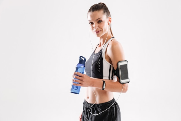 Счастливая женщина фитнеса в наушниках стоя и держа бутылка с водой