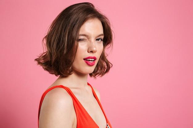 Портрет крупным планом очаровательной брюнетки с ярким макияжем подмигивает одному глазу, пока