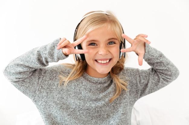 Крупным планом смешная маленькая девочка в наушниках, показывая мир жест с двумя руками, смотрю на камеру