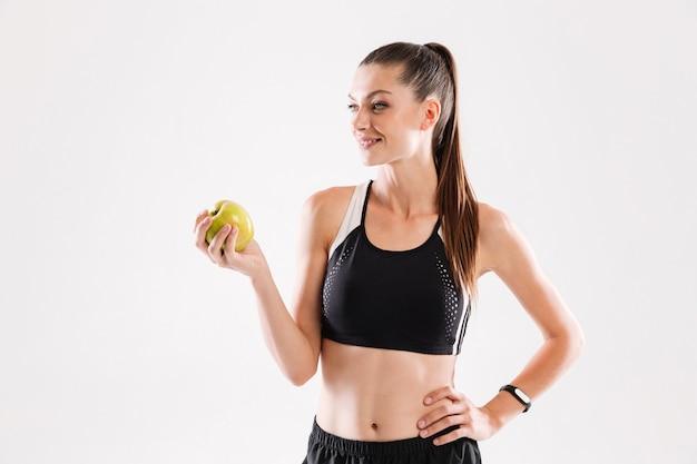 Портрет здоровой красивой спортсменки, держащей зеленое яблоко