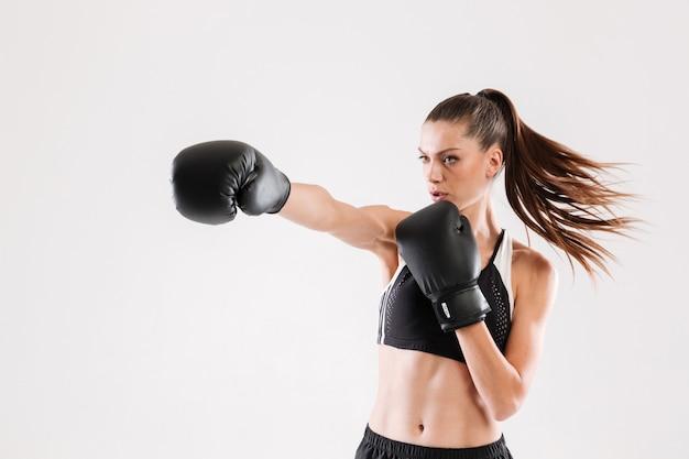 Портрет молодой мотивированной женщины делают бокс