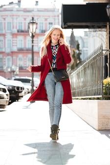 電話で話している素晴らしいファッションの若いブロンドの女性。