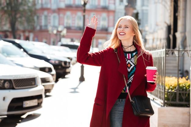 素晴らしいファッションの若いブロンドの女性が手を振ってコーヒーを飲みます。