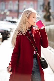野外を歩いている深刻なファッションの若いブロンドの女性