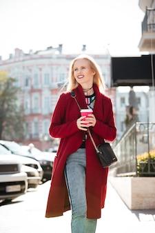 野外を歩いている笑顔のファッションの若いブロンドの女性