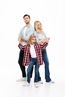 一緒に立っている若い美しい家族の完全な長さの肖像画