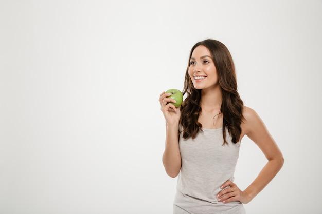 白で隔離された長い茶色の髪立っている健康な女性の肖像画、緑のジューシーなリンゴを試飲