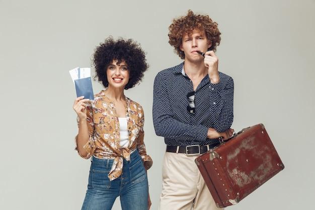 レトロな愛情のあるカップルはスーツケースのパスポートとチケットを保持しています。