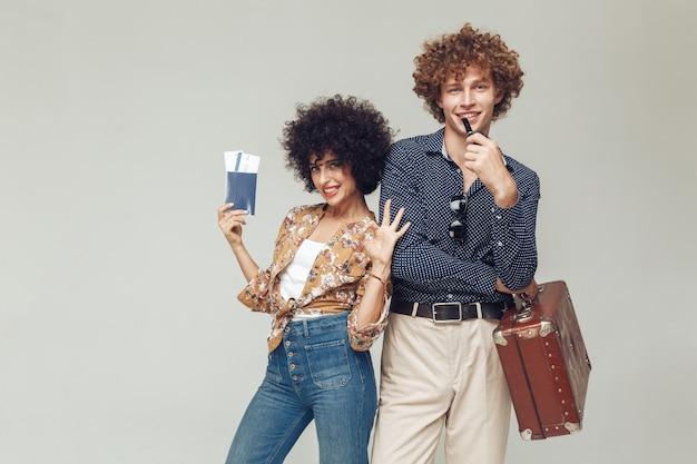 Ретро влюбленная пара чемодан паспорт и билеты.