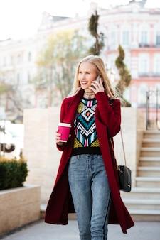 電話で話している屋外を歩いて幸せな若い白人女性