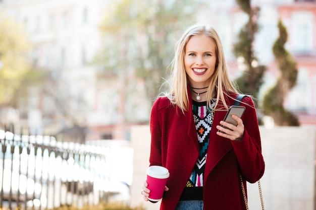 屋外チャットを歩いて笑顔の若い白人女性