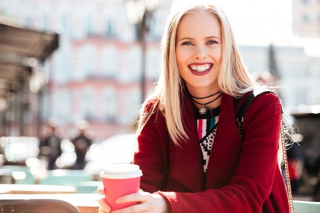 屋外のコーヒーを飲みながらカフェに座っている陽気な女性