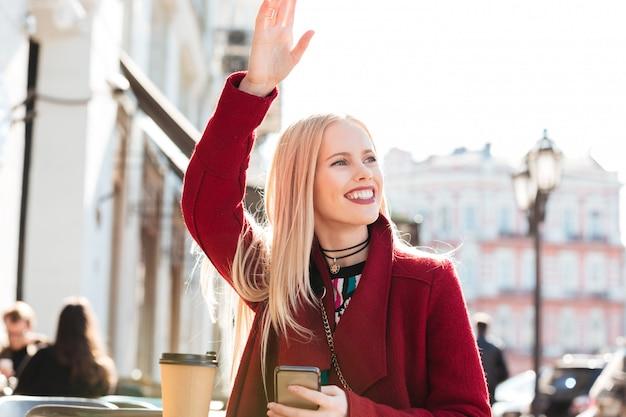 チャットと手を振っているカフェに座って幸せな若い白人女性
