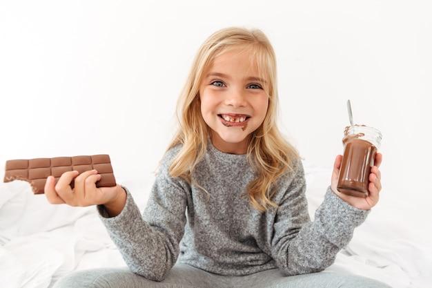 Милая смешная девушка держит шоколадку и показывает ее грязные зубы