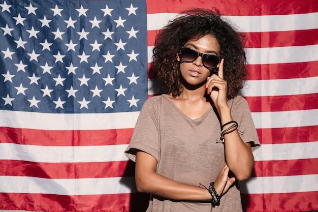 Серьезная африканская молодая леди стоит над флагом сша
