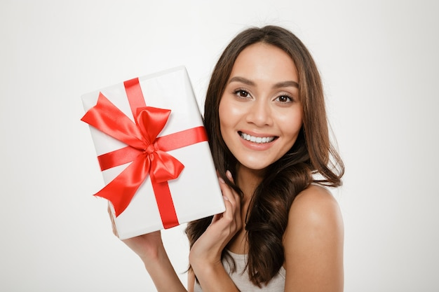 白で分離された幸福と喜びを表現するカメラに赤い弓とギフト包装箱を示す陽気な女性の写真をクローズアップ