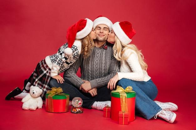 分離された座っているクリスマスの帽子を着てかわいい陽気な若い家族