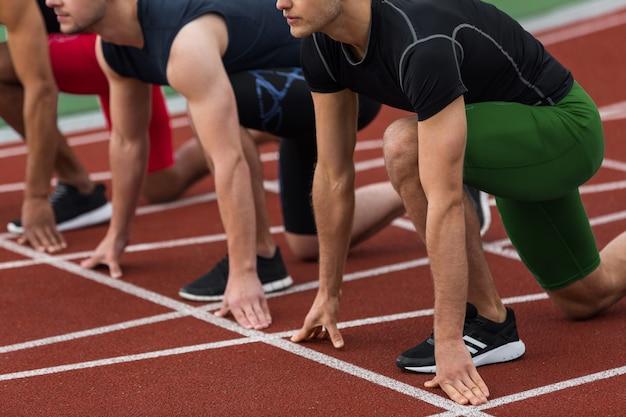 Обрезанное изображение многонациональной группы спортсменов, готовых к запуску