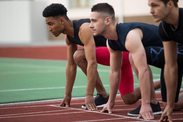 Концентрированная многонациональная группа спортсменов, готовая к бегу