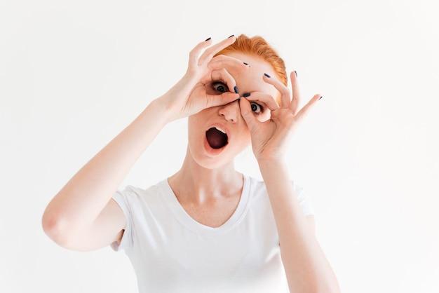 Смешная рыжая женщина делает маску из своей руки