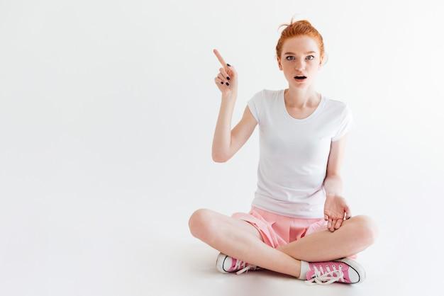 Удивленная рыжая девушка сидит на полу и смотрит, указывая в сторону