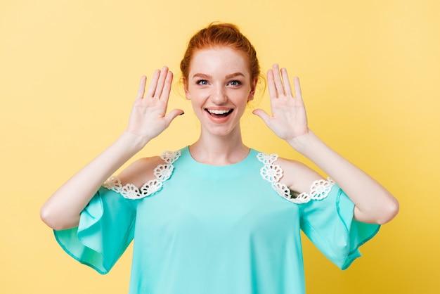 Счастливая рыжая женщина в платье, держась за руки возле ушей