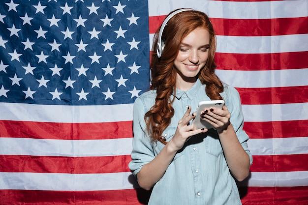Счастливый рыжий молодой леди прослушивания музыки