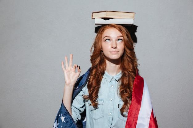 アメリカの国旗を身に着けている頭の上の本を保持している面白い赤毛の若い女性