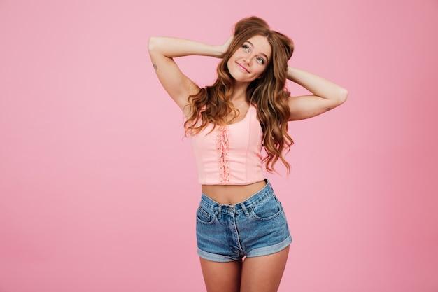 Портрет довольно улыбается женщина в летней одежде позирует