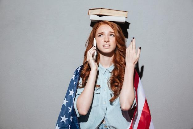Путать рыжий молодой леди, держа книгу на голове