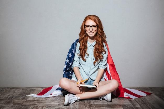 ノートを保持している幸せな赤毛の若い女性