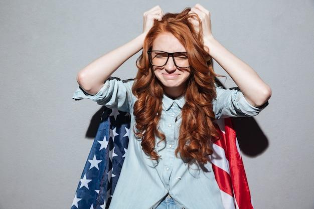 ノート用紙を保持している混乱している赤毛の若い女性