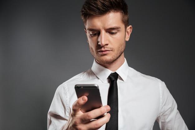 Портрет молодого серьезного бизнесмена используя мобильный телефон