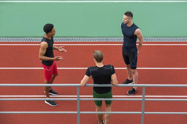 Многонациональная группа спортсменов разговаривает друг с другом