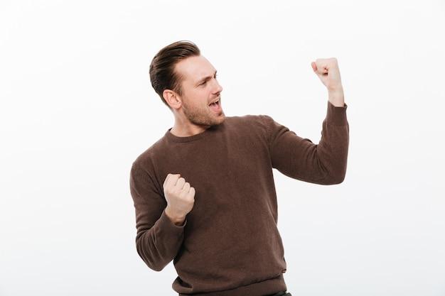 興奮した若い男が勝者ジェスチャーを作ります。